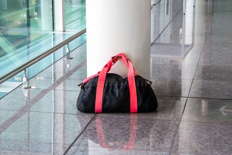 可疑黑和红色袋子在一个空的大厅剩下未看管 恐怖主义和公共安全的概念 危险无主 免版税库存照片