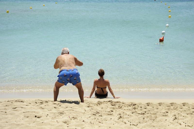 可笑和滑稽的情况 一个年长人为后面观点的美女照相坐海滩 免版税图库摄影