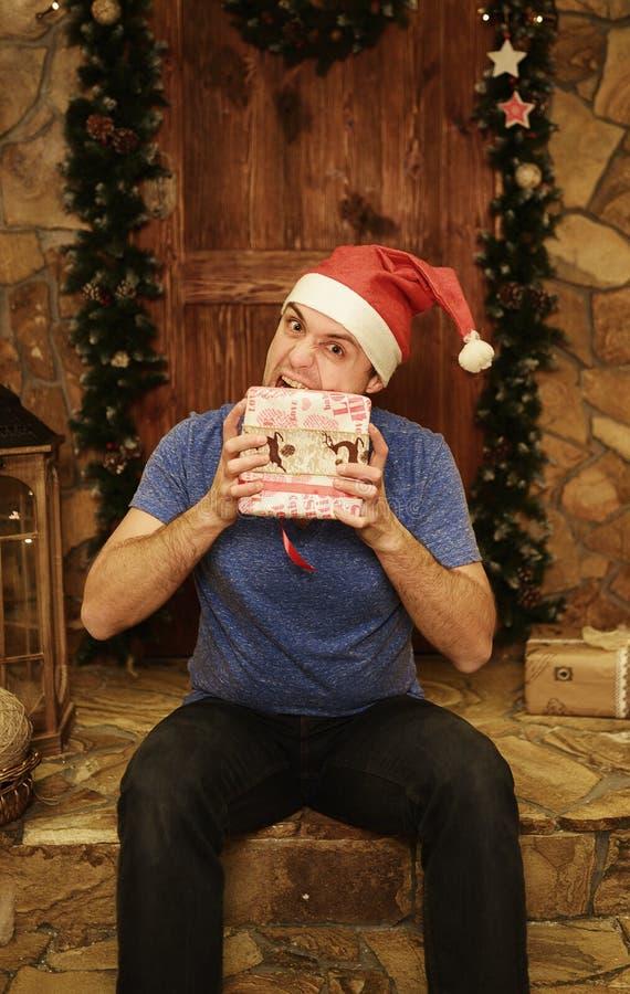 年轻可笑的人惊奇对圣诞节礼物 库存图片
