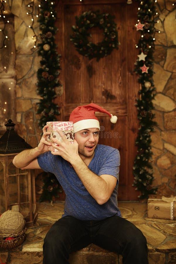 年轻可笑的人惊奇对圣诞节礼物 免版税库存图片