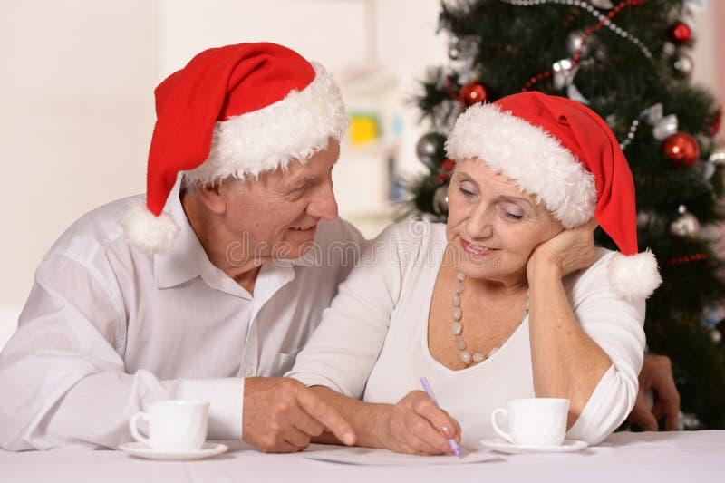 可笑的老有茶的夫妇佩带的圣诞节假日盖帽画象  库存图片