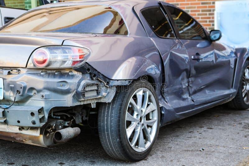 可能仍然驾驶的非常被击毁的银色汽车在商店-正确的背面图停放了-它被击中了的地方 免版税库存图片