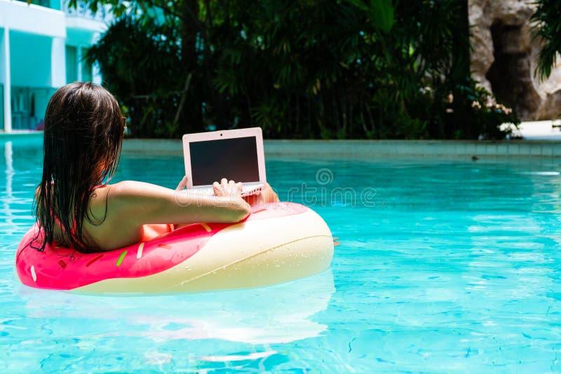 可膨胀的圈子在水池与膝上型计算机,做自由职业者的概念和休闲的女孩 免版税库存照片