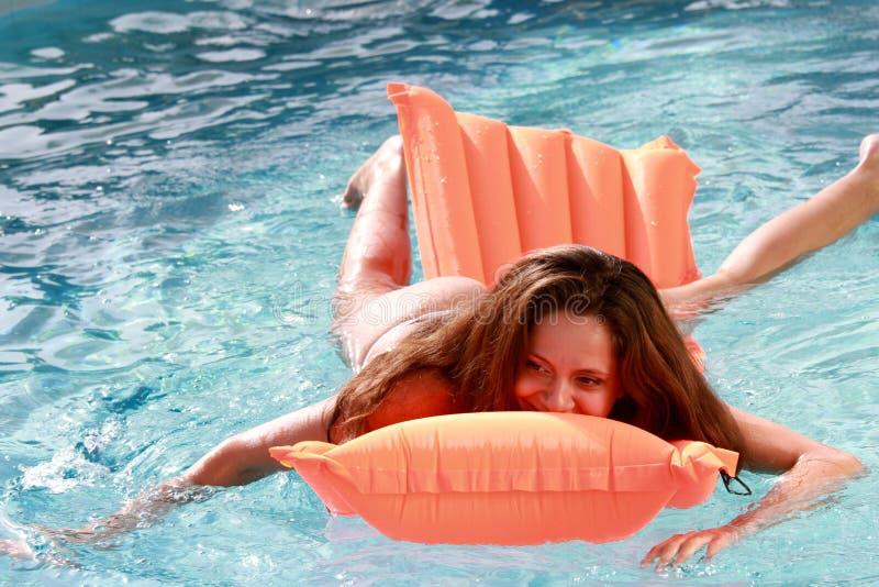 可膨胀的床垫的女孩在水池 免版税图库摄影