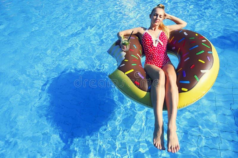 可膨胀的床垫的少妇在游泳池 免版税库存照片
