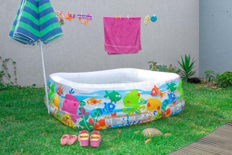 可膨胀的水池在庭院里,有伞的 图库摄影