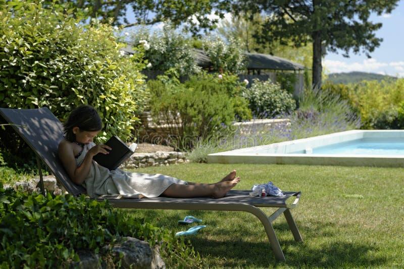可躺式椅读书的女孩 免版税库存图片