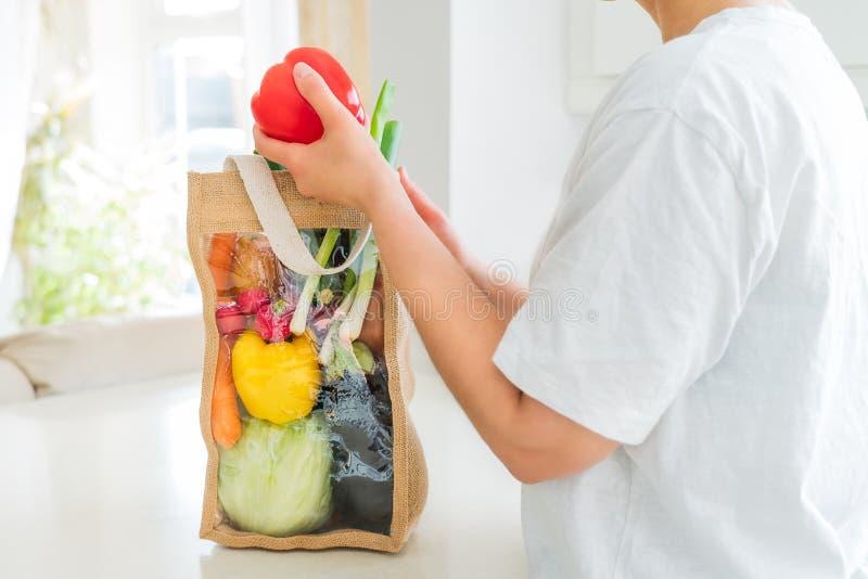 可重复使用的蔬菜袋包装白餐桌上不带红色铃纸的脸妇 库存照片