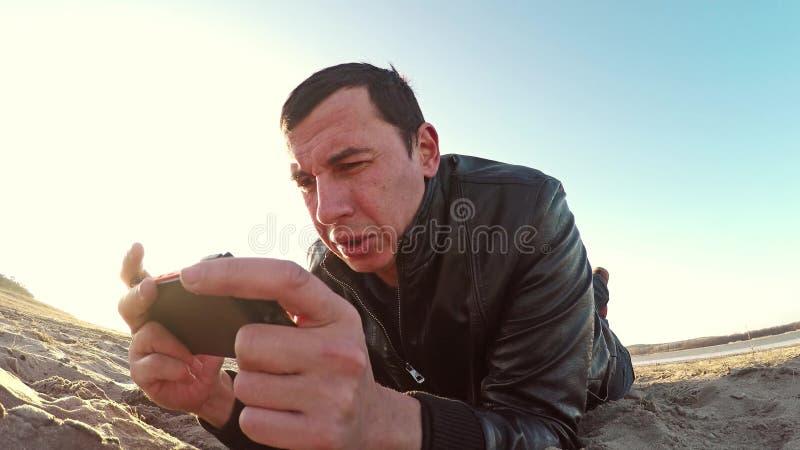 可移植的控制台 人在沙子和戏剧说谎在便携式的阳光控制台在生活方式日落 库存照片
