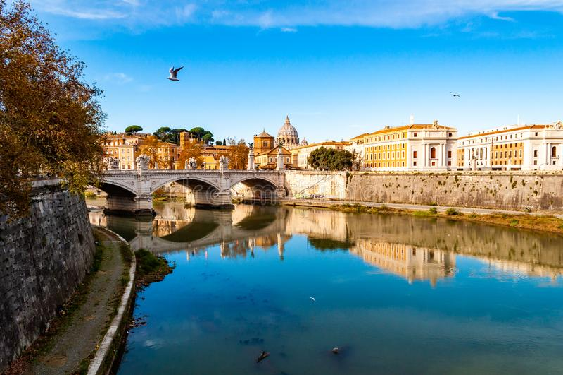 台伯河河小河、蓬特维托里奥・埃曼努埃莱・迪・萨伏伊II桥梁、飞行的与圣皮特圣徒・彼得圆顶的海鸥和罗马都市风景视图在 图库摄影