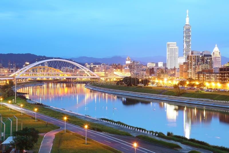 台北市的夜场面有桥梁和美好的反射的 与信益dist的台北都市风景在河沿的黄昏  免版税库存图片