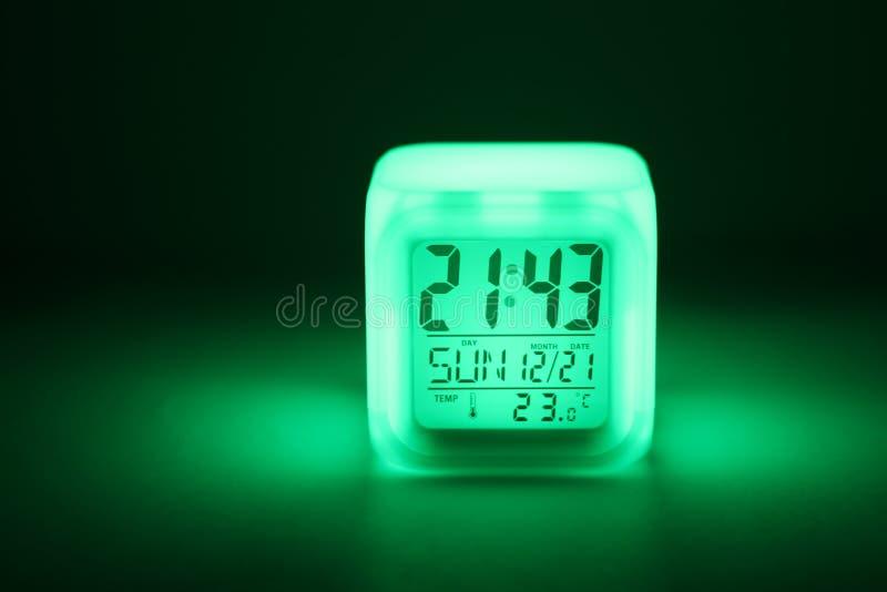 台式时钟在黑暗中 机场箭头绿灯符号 免版税库存照片