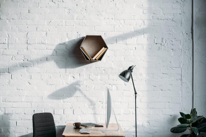 台灯、计算机和架子在墙壁 库存照片