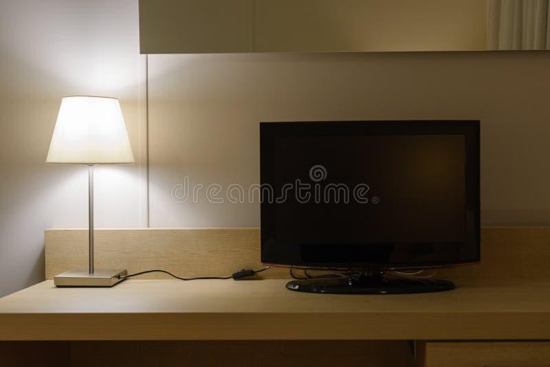 台灯和一台电视机在一张木桌 免版税库存照片