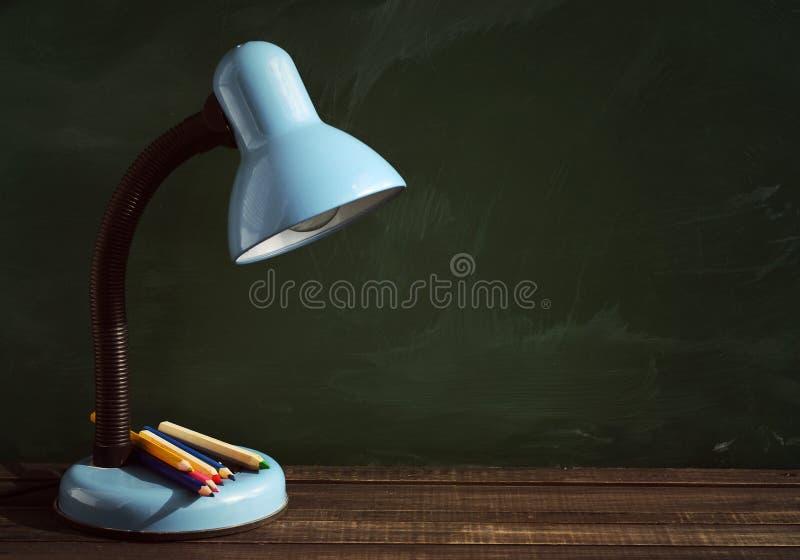 台灯和色的铅笔在木表面 免版税库存图片