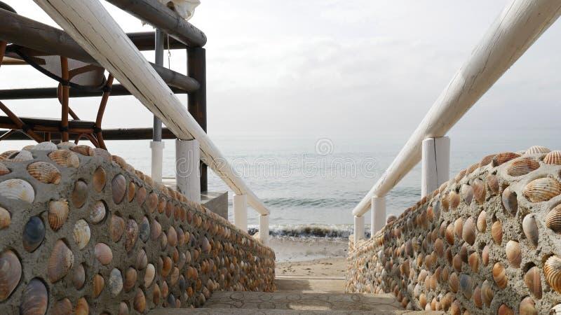 台阶导致海的由壳和木扶手栏杆制成 库存照片