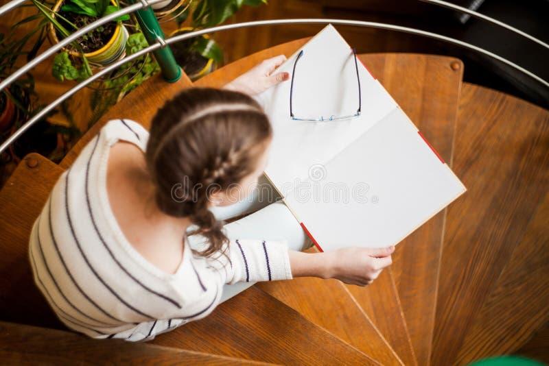 台阶的女孩读书的 免版税库存照片