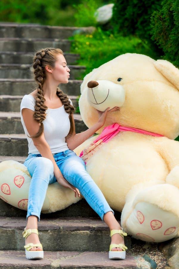 台阶的愉快的女孩在有一个巨大的玩具熊的公园 免版税库存图片