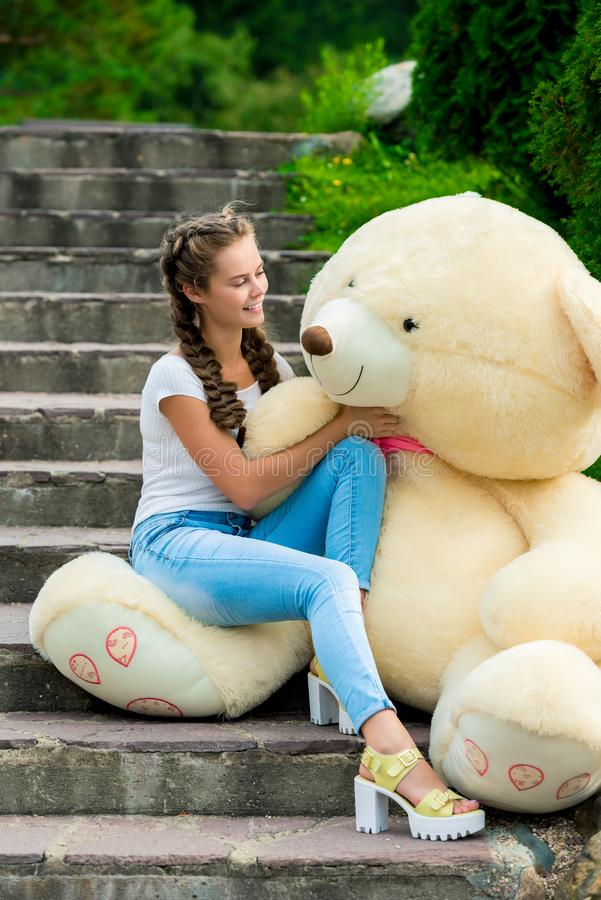 台阶的美丽的女孩在公园敬佩她的巨大 免版税库存照片