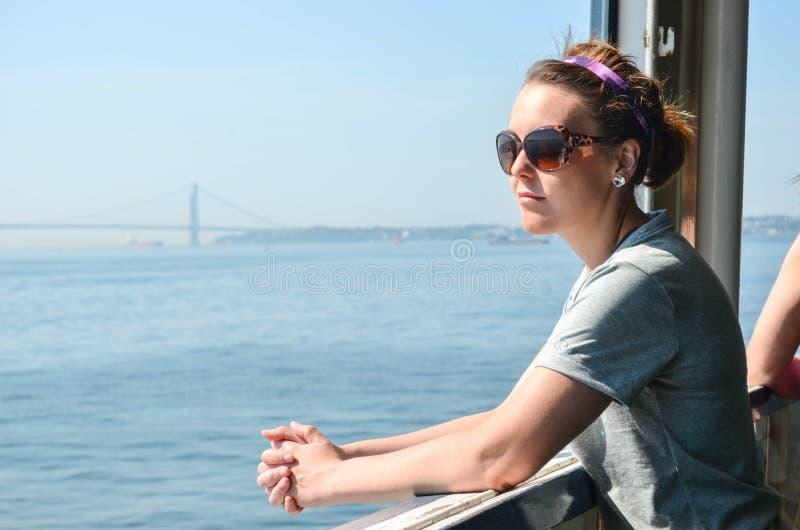 史泰登岛渡轮的一位女性乘客敬佩NYC地平线的看法 库存照片