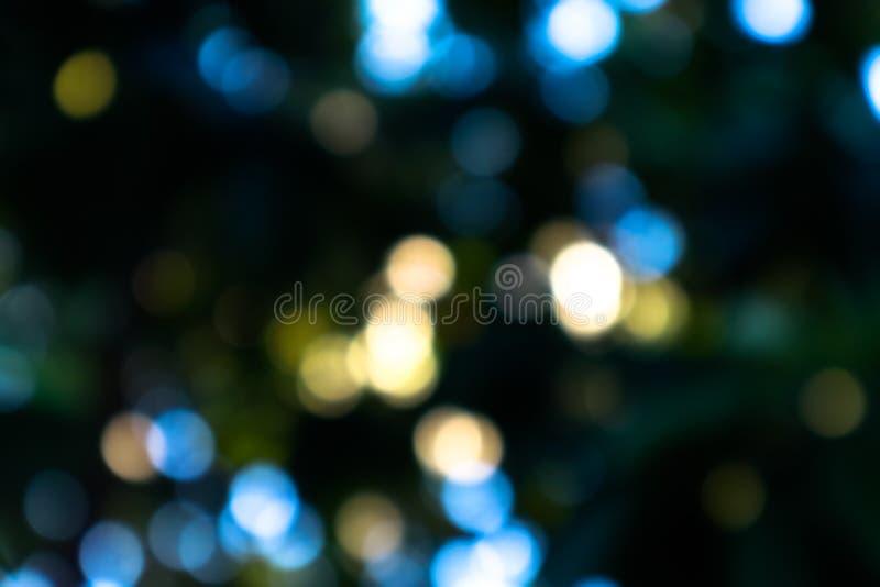 叶子和阳光Bokeh在黑背景 免版税库存照片