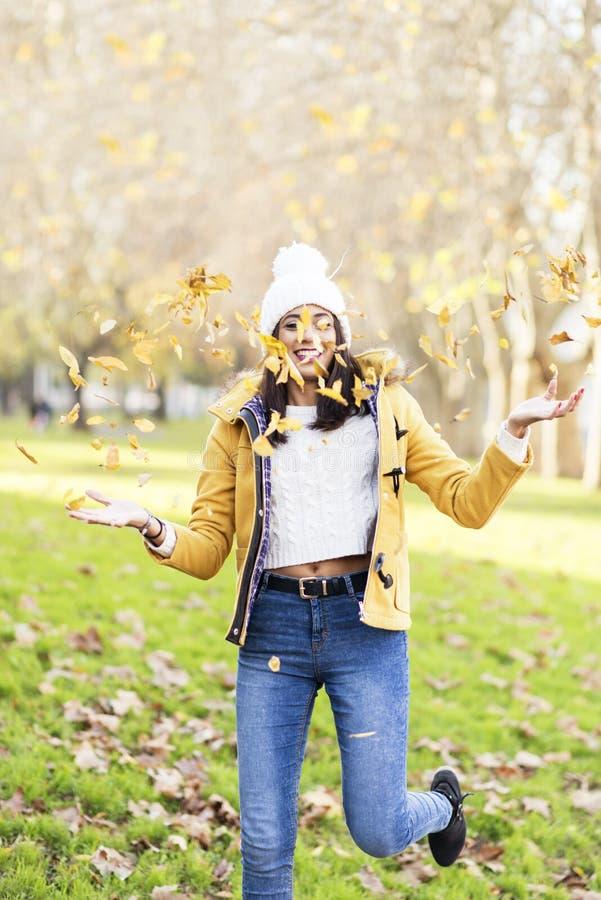 叶子快乐的少妇playng在公园 免版税图库摄影