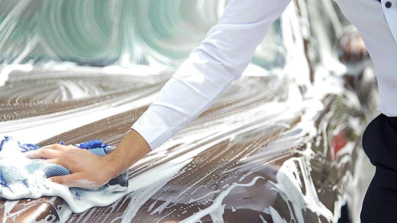 司机周到清洁汽车,优良品质洗涤服务,汽车事务 库存图片