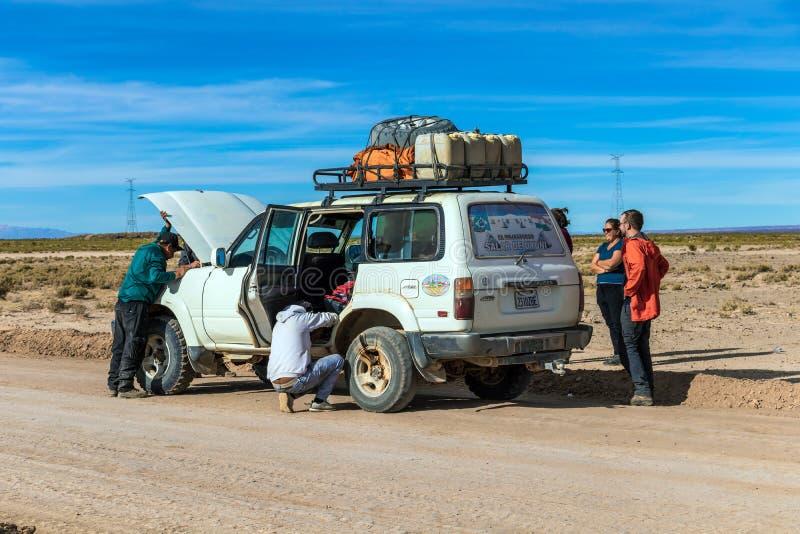 司机和游人在4x4在玻利维亚人阿尔蒂普拉诺高原,玻利维亚的吉普游览时固定残破的汽车 库存照片