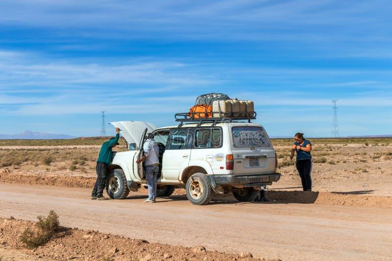 司机和游人在4x4在玻利维亚人阿尔蒂普拉诺高原,玻利维亚的吉普游览时固定残破的汽车 免版税库存照片