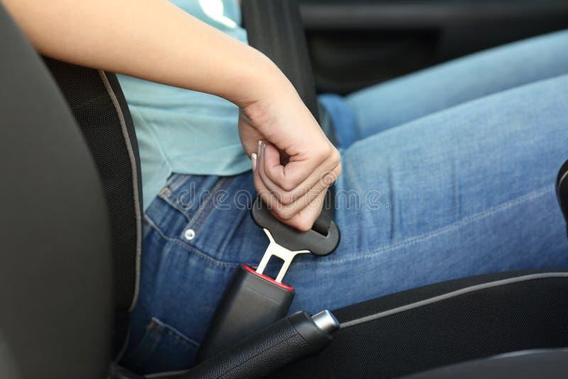 司机手在汽车的紧固安全带 免版税图库摄影