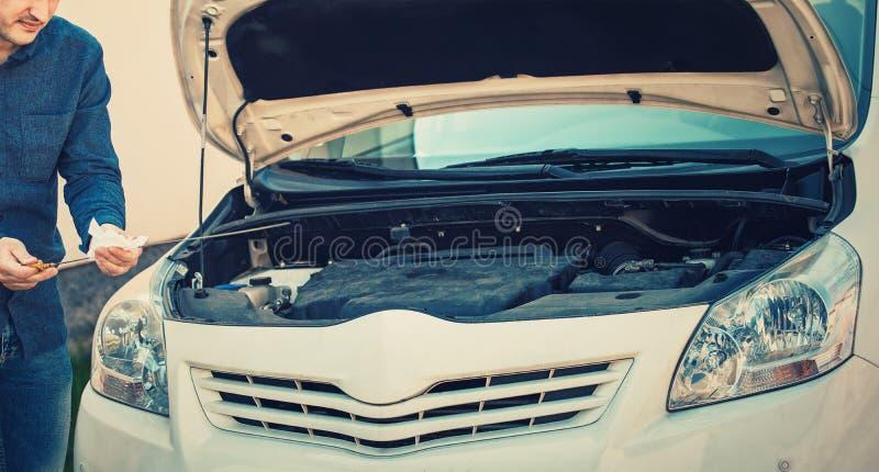 司机检查在发动机的油面 车修理服务,汽车机械师工作 年轻人驾驶人有问题,看 免版税库存照片