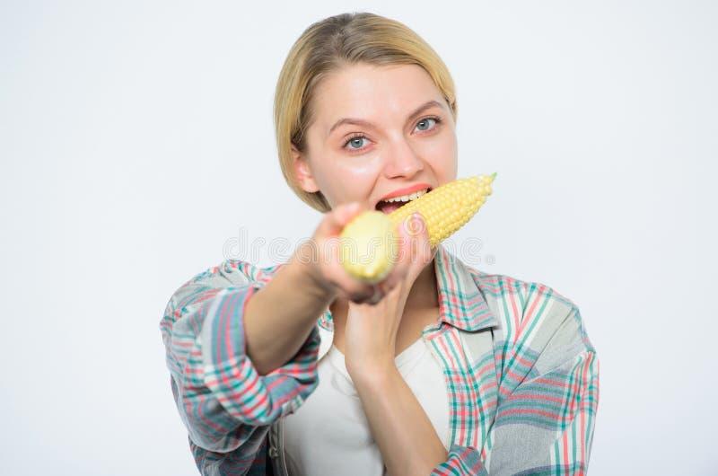 吃一个可口棒子的妇女 吃玉米的愉快的妇女 种田菜的收获,农夫女孩用玉米 库存照片