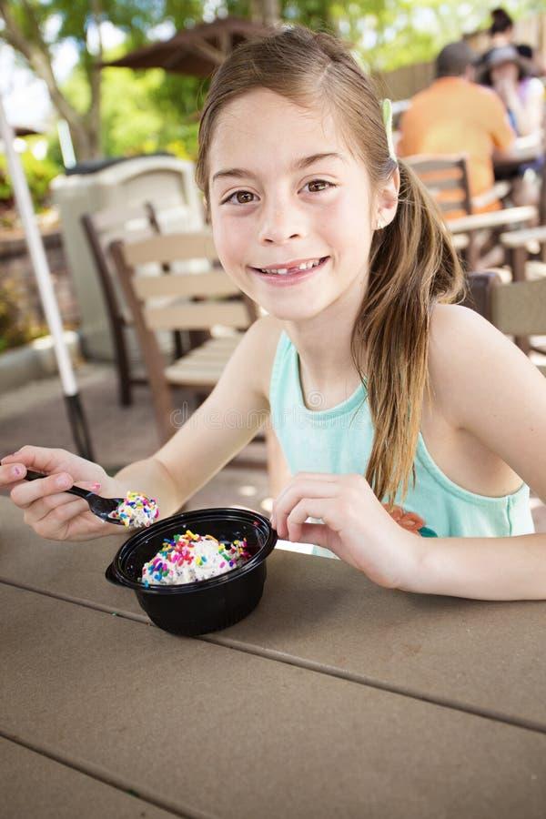 吃一个可口碗冰淇凌的逗人喜爱的微笑的小女孩在一个室外咖啡馆 免版税库存照片