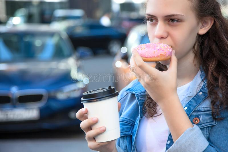 吃一个多福饼用在街道的咖啡的青少年的女孩 免版税库存照片