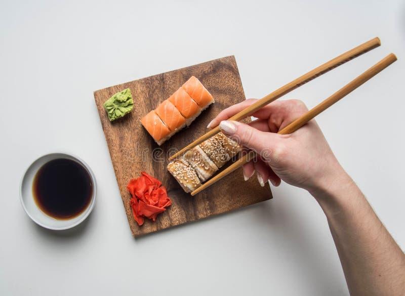 吃一个开胃寿司集合用姜、酱油和山葵的女孩在白色背景 免版税库存照片