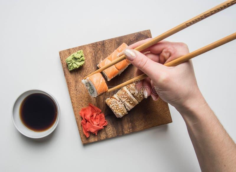 吃一个开胃寿司集合用姜、酱油和山葵的女孩在白色背景 免版税图库摄影