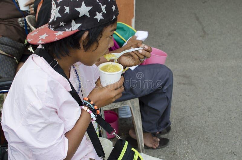 吃一个杯子稀饭的轮椅女性叫化子 免版税库存照片