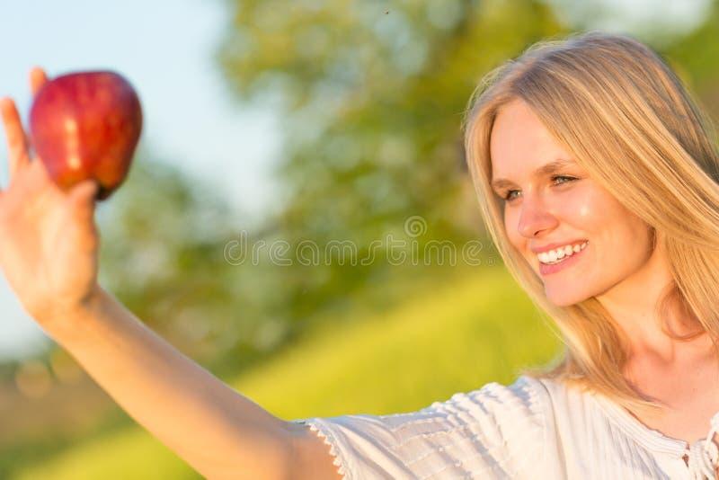 吃一个红色苹果的美丽的微笑的妇女在公园 室外的本质 免版税库存照片