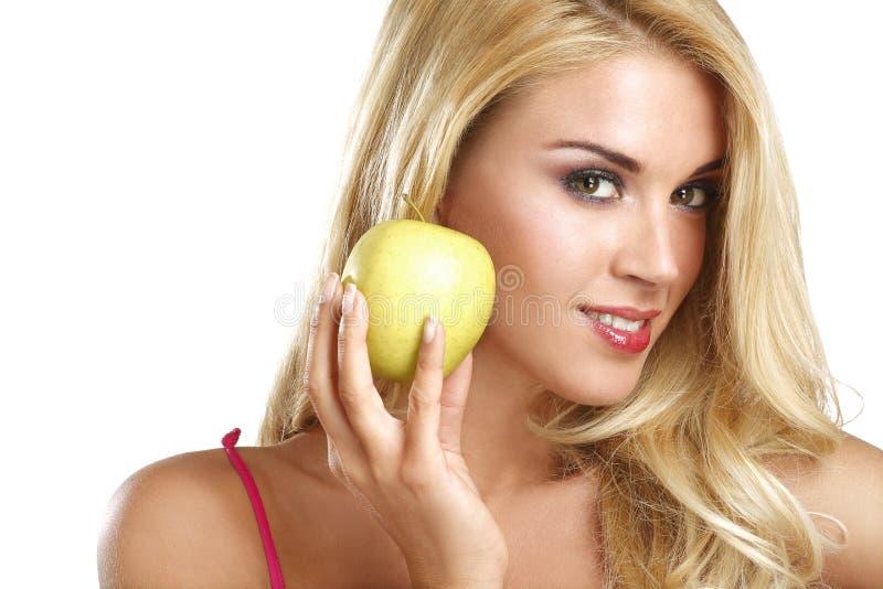 吃一个绿色苹果的年轻愉快的美丽的女孩 图库摄影