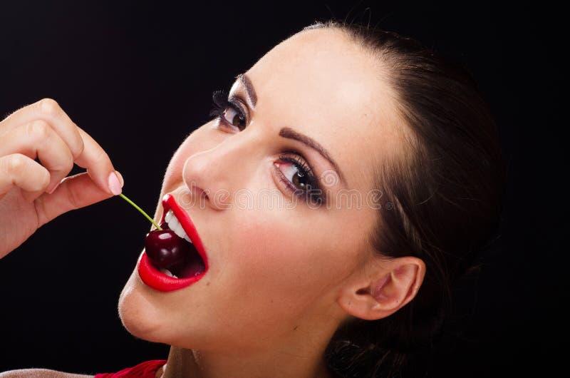 吃一棵深红樱桃的美丽,时髦的妇女 图库摄影