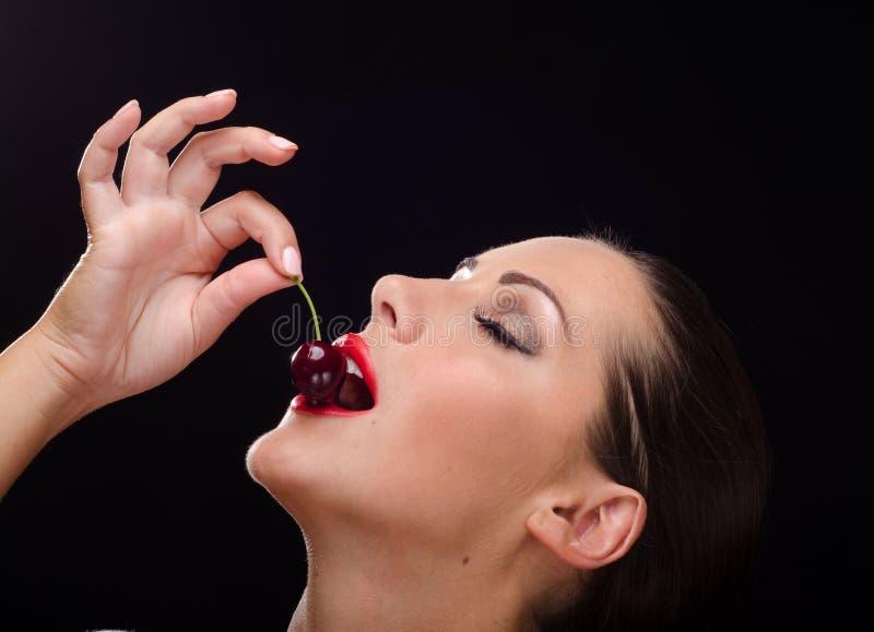 吃一棵深红樱桃的美丽,时髦的妇女 免版税库存图片