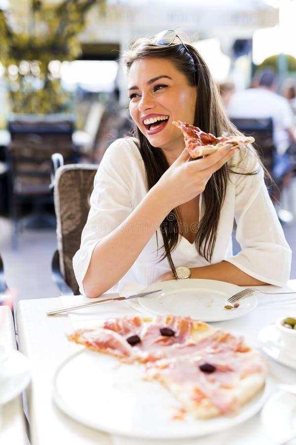吃一片薄饼的美丽的少妇在餐馆 免版税库存照片