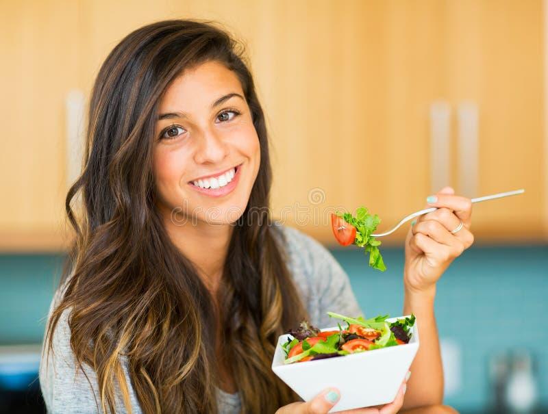 吃一碗健康有机沙拉的美丽的少妇 库存照片