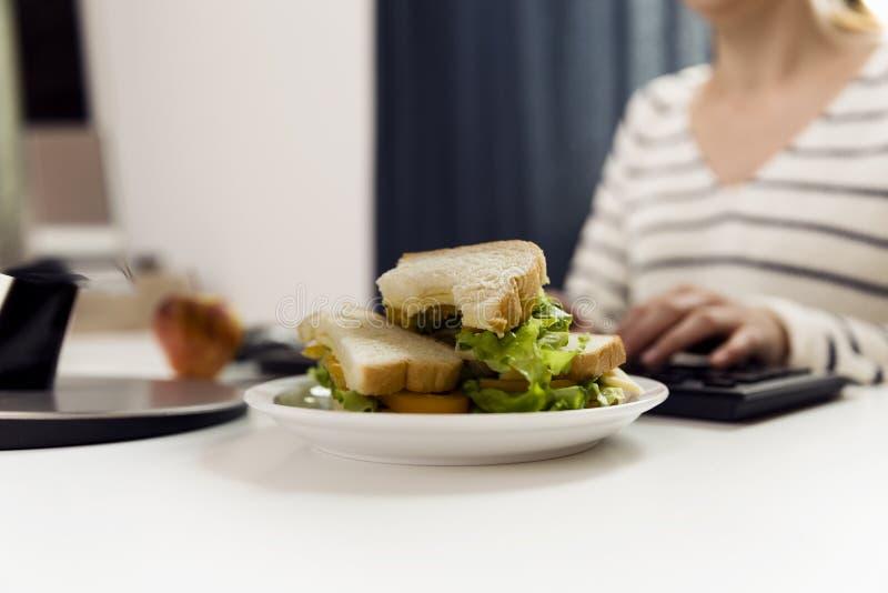 吃三明治的妇女,当工作时 从新鲜的多士w的三明治 库存图片