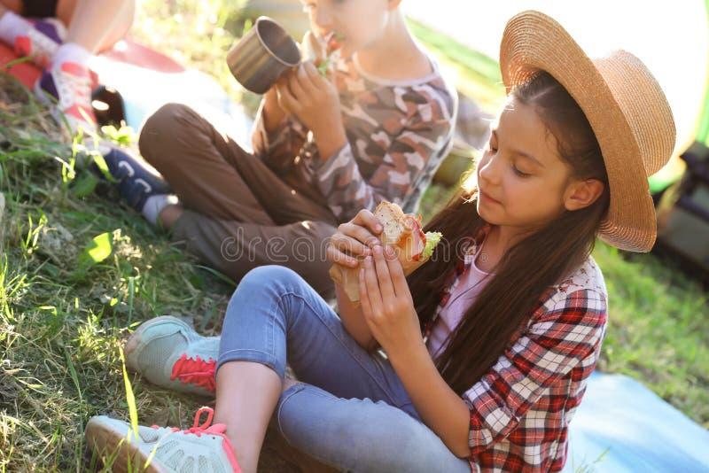 吃三明治的小女孩户外 库存图片