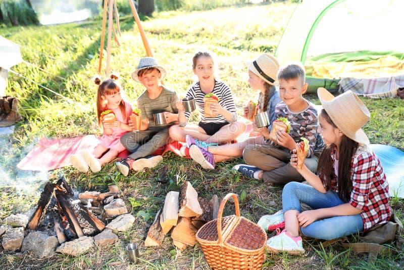 吃三明治的小孩临近篝火 免版税库存照片