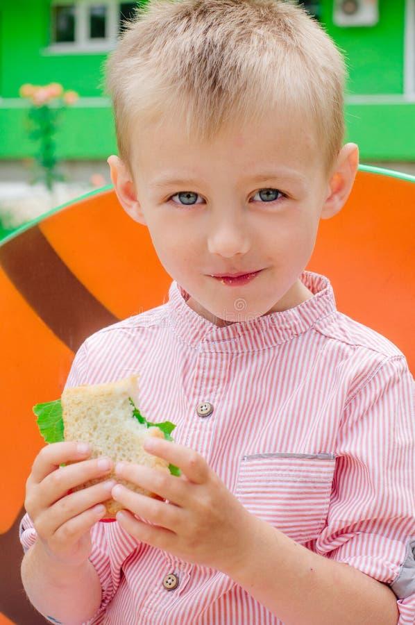吃三明治的微笑的男小学生坐在小学附近 免版税库存照片