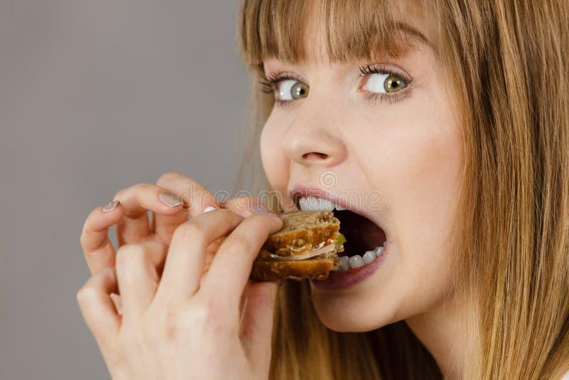 吃三明治的妇女,采取叮咬 免版税库存照片