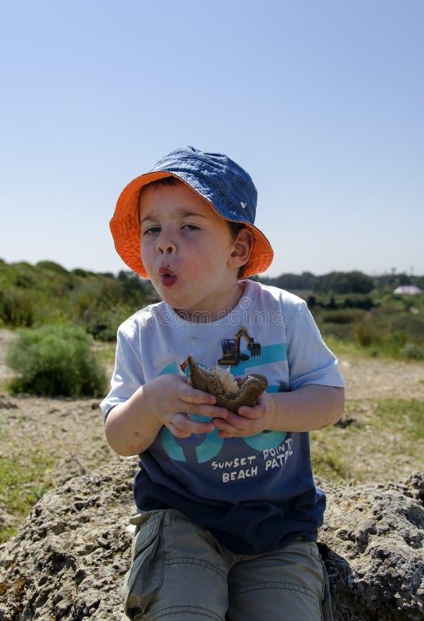 吃三明治的小孩在自然保护 免版税库存照片