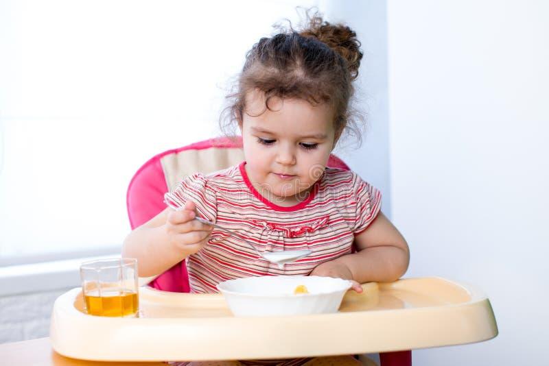 吃与匙子的俏丽的孩子 免版税库存图片